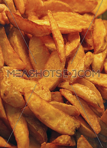 Unhealthy ready to eat deep fried potato or baked potato wedges chips with skins close up, high angle view
