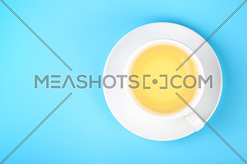 Close up one full white cup of green oolong or herbal tea on saucer over pastel blue paper background, elevated top view, directly above