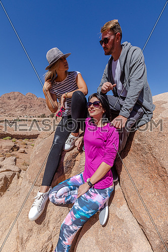 a group of tourists standing while exploring Sinai Mountain in wadi Freij at day.