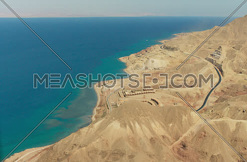 Arial shot for a desert mountain by the sea at day