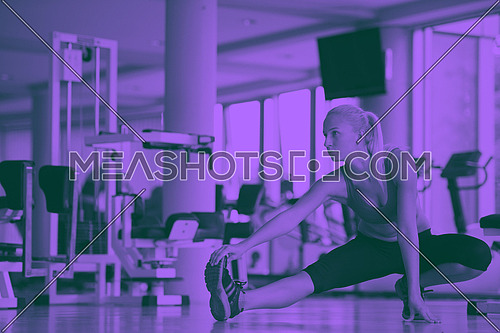 Cute young woman stretching and warming up for her training at a gym duo tone