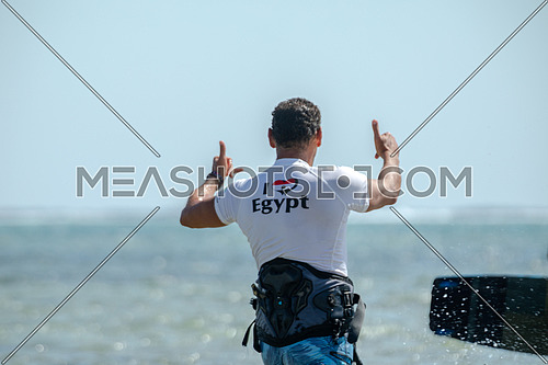Male Kite surfing instructor wearing a white shirt wiritten on ( I Love Egypt) and  Egyptian flag heart shaped giving instruction to surfers  in the Red Sea by day.