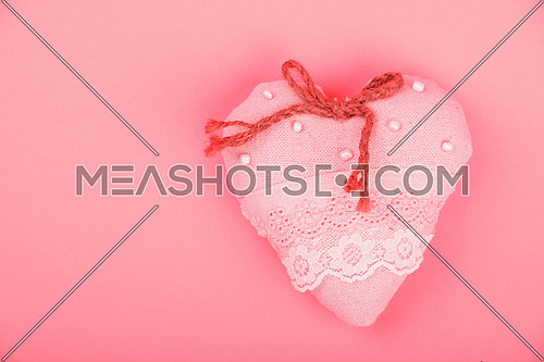 Valentine template, handmade pink toy textile lace heart with burlap jute bow, beads and copy space on paper background