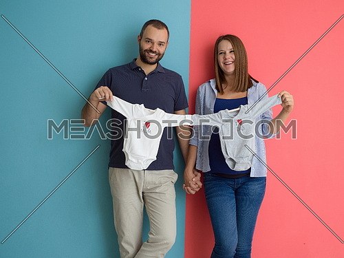 Beautiful pregnant woman and her husband expecting baby holding baby bodysuits and smiling over colorful background