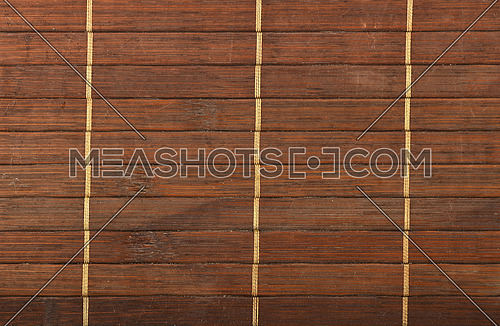 Bamboo wooden dark brown used wicker braided mat with light yellow thread background