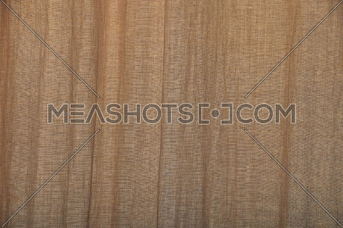 Natural brown burlap jute sackcloth bagging canvas curtain with waves of pleats and folds, texture pattern background