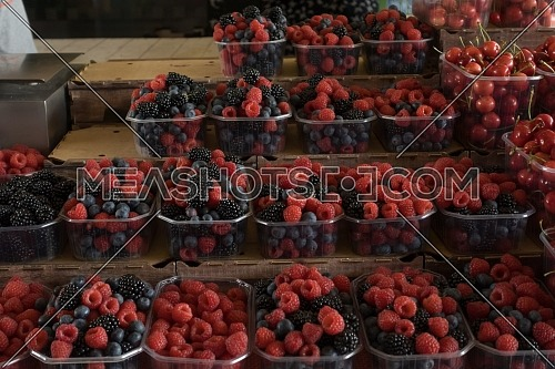 Fresh berries on box sale at the market.blueberries, raspberry and blackberries on a market stall.