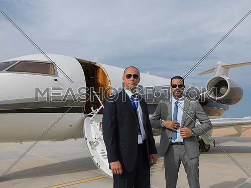 portrait of two successful middle eastern businessman in front of private airplane