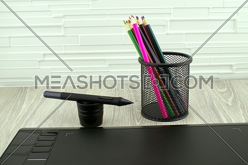Digital stylus pen near digital graphic tablet for illustrators and designers opposite colored drawing pencils. Free space for text
