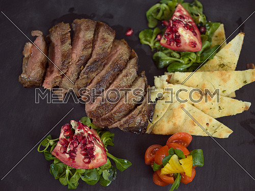 Juicy slices of grilled steak  with vegetables on a wooden board, top view