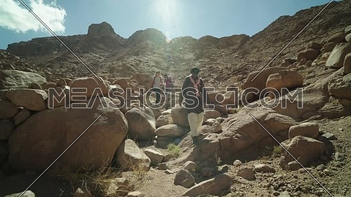 Reveal shot for group of tourists climbing down big rocks with bedouin guide to explore Sinai Mountain for wadi Freij at day.