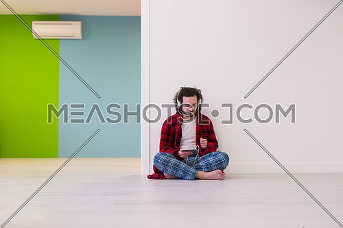 Young handsome man enjoying music through headphones,sitting on the floor at home