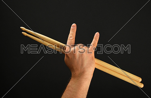 Man hand holding two drumsticks with devil horns rock metal gesture sign over black background, back view