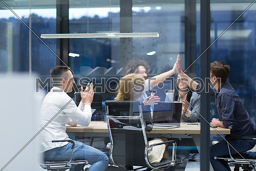 Group of young business people looking happy while celebrating success at their working places in startup office
