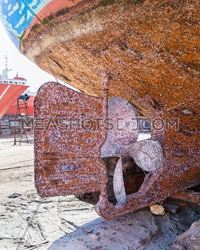 Propeller of ship placed on bridging during reconstruction work in old shipbuilding plant on coast