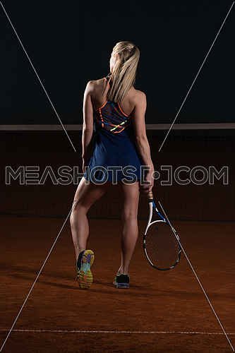 Portrait Of Woman Tennis Player With Racket Ready To Hit A Tennis Ball - Back View