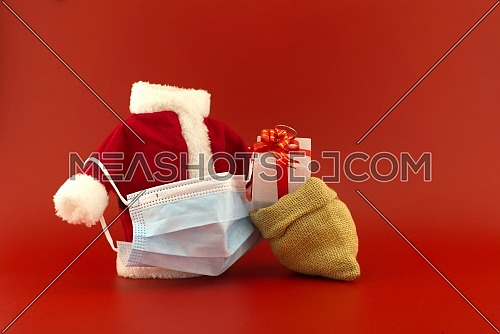 Christmas in pandemic concept still life with miniature santa costume, gift box and surgical face mask all isolated on red background