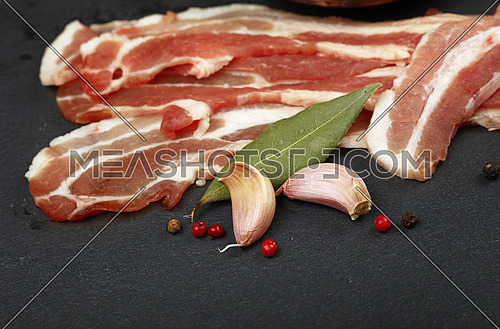 Raw pork bacon slices, rashers, spices, rose peppercorns, garlic and laurel bay leaves on black slate board, close up, high angle view