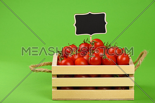 Fresh red ripe cherry tomatoes in small wooden box with black chalkboard price sign tag over green background