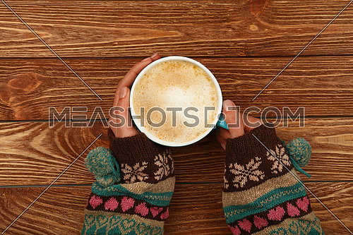 Close up two woman hands hold and hug big full cup of latte cappuccino coffee with milk froth over brown wooden table, elevated top view, directly above