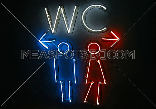 Close up glowing blue and red neon lights of WC toilet sign with directions to men and women, left and right arrows, over dark black wall background
