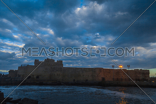 Long Shot outside Citadel of Qaitbay shows sea waves at Cloudy day to night