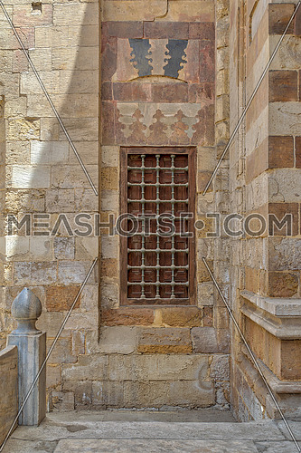 Grunge wooden aged window with iron bars on exterior stone bricks wall of Amir Aqsunqur Mosque (Blue Mosque), Medieval Cairo, Egypt