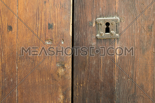 Rusted keyhole over an old weathered wooden grungy door
