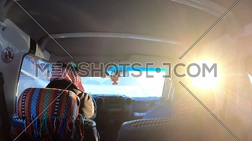 Inside shot from a car driving on the route in Sinai showing Bedouin driver and male tourist at sunset