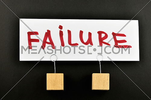 Failure, One big white paper note with two wooden holders and red letters, isolated on black paper background for presentation