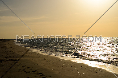 Sunset magical golden hour on the beach and foot steps appears on the sand in a magical view
