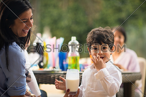 child drinking milk with mother and sister