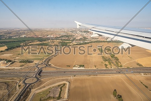 Looking through aircraft window during flight. Aircraft wing over blue skies,crossroad and cityscape background .Copy space.
