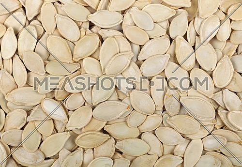 Background pattern of raw white pumpkin seeds (pepitas) close up, elevated top view