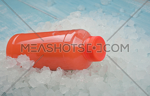 Close up one plastic PET bottle of fresh pink grapefruit juice over background of crushed ice, high angle view