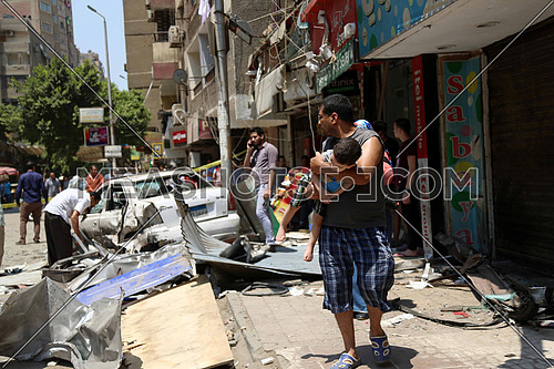 Father carrying his son and away from the site of a gas cylinder explosion led to the destruction of 5 shops and 3 cars on Hassanin Desouk street 21Jul 2017