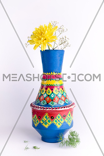 Still life composition of colorful pottery vase with a yellow flower on white background