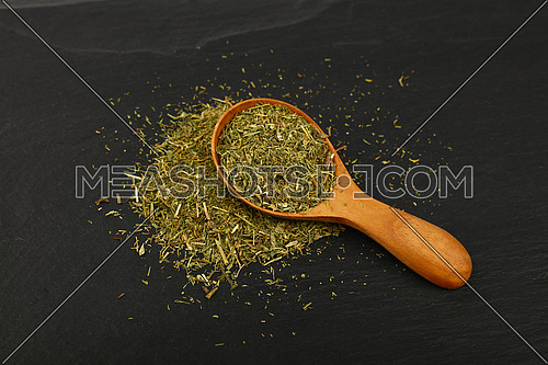 Close up one wooden scoop spoon full of green dried herbs, dill or marjoram on background of black slate board, high angle view