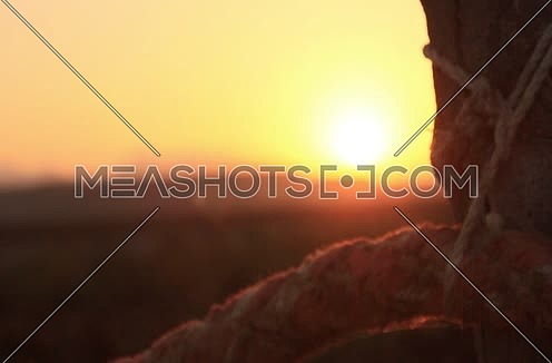 Long shot for a mountain and the sun flares with rope cutting sun light at dusk time at wadi lahmi at day - 5D