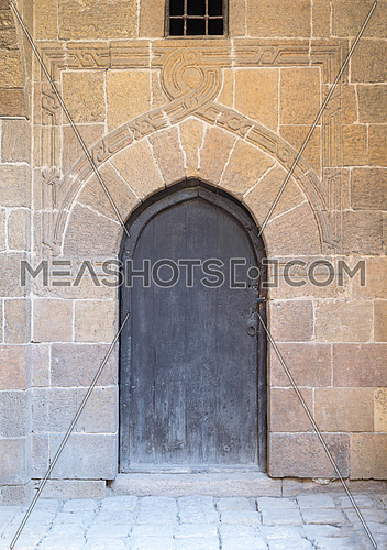 Wooden aged vaulted ornate door and stone wall, Medieval Cairo, Egypt