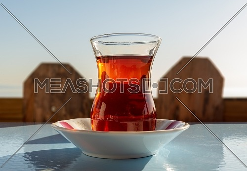 Glass of traditional Turkish tea, with background of wooden fence and sky, Istanbul, Turkey