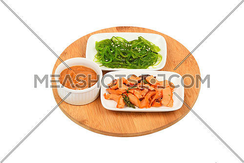 Two portions of seafood marinated salad with octopus cuttlefish and seaweeds in with sauce on round wooden board