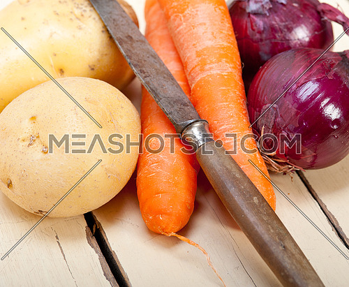 basic vegetable ingredients carrot potato onion on a rustic wood table