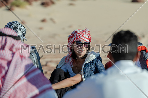 Reveal shot for group of tourists sitting with bedouin guides exploring Sinai Trail from Ain Hodouda at day.
