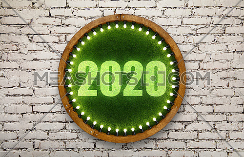 Close up 2020 sign on round shape wooden ring light frame with lightbulbs and backdrop of illuminated vivid green plastic artificial grass over grey brick wall background
