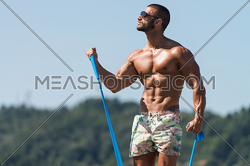 Handsome Guy Working Out With Rubber Outdoors