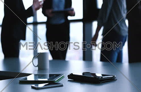 Devices on table with business people in background in modern office building