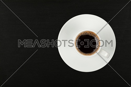 Close up one white cup full of instant coffee on saucer over black chalkboard background, elevated top view, directly above