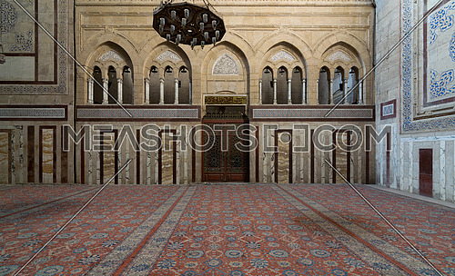 Interior shot of Al Rifaii Mosque (Royal Mosque) with iron chandelier, decorated marble wall and ornate wooden door, located in front the Cairo Citadel, Cairo, Egypt