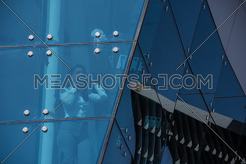 Outdoor shoot showing a female executive talking on the phone through the glass front of a corporate offices building with a background of blue sky